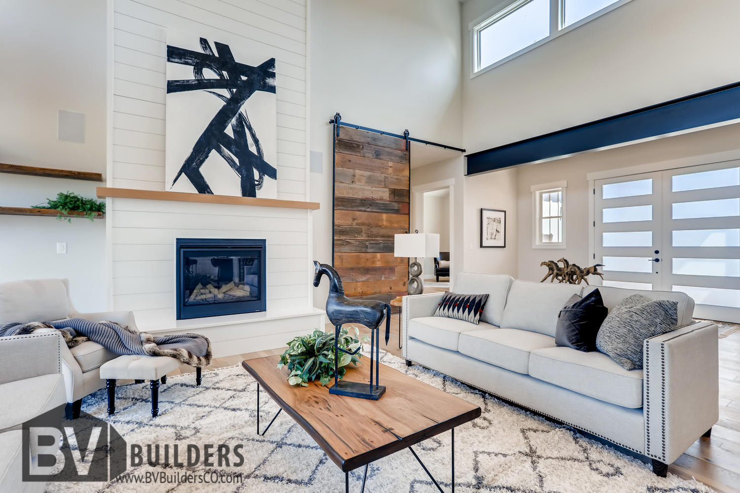 Modern farmhouse great room living room with exposed steel beams, reclaimed wood barn door and shiplap fireplace