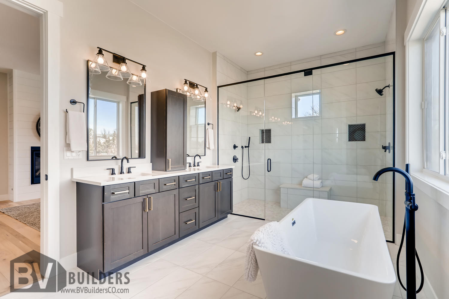 Modern farmhouse master bathroom with double vanity, soaker tub and glass shower door