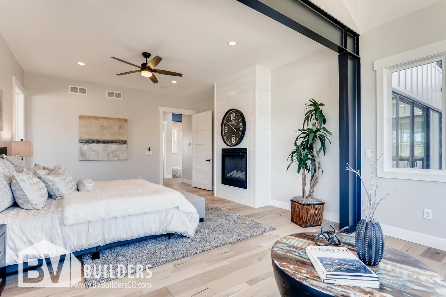 Modern farmhouse master bedroom with exposed steel beams and shiplap fireplace