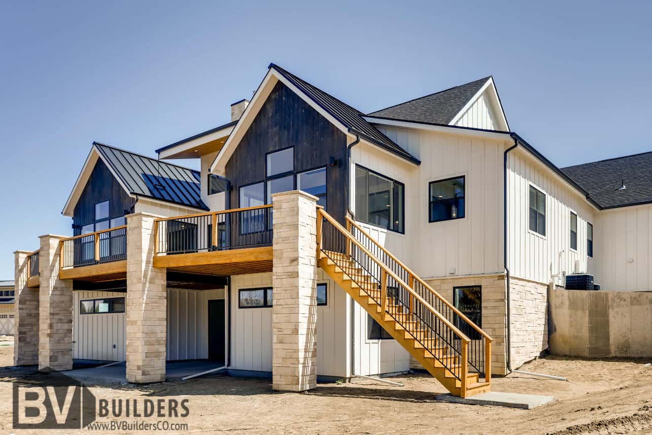 Modern farmhouse with a wood deck Thermory wood vertical siding and walkout basement