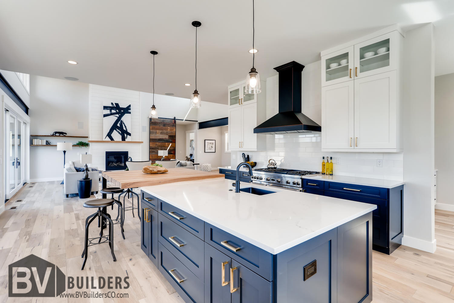 Modern farmhouse kitchen with dark blue cabinets, white subway tile backsplash, butcher block bar and Thermador range