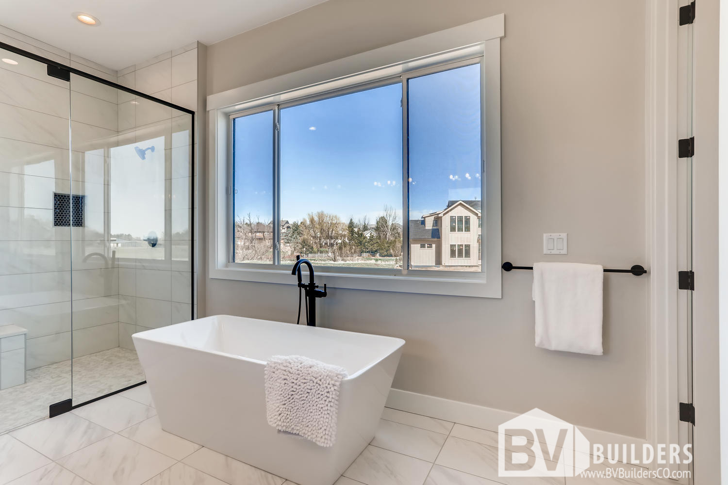 Modern farmhouse master bathroom with soaker tub and glass shower door