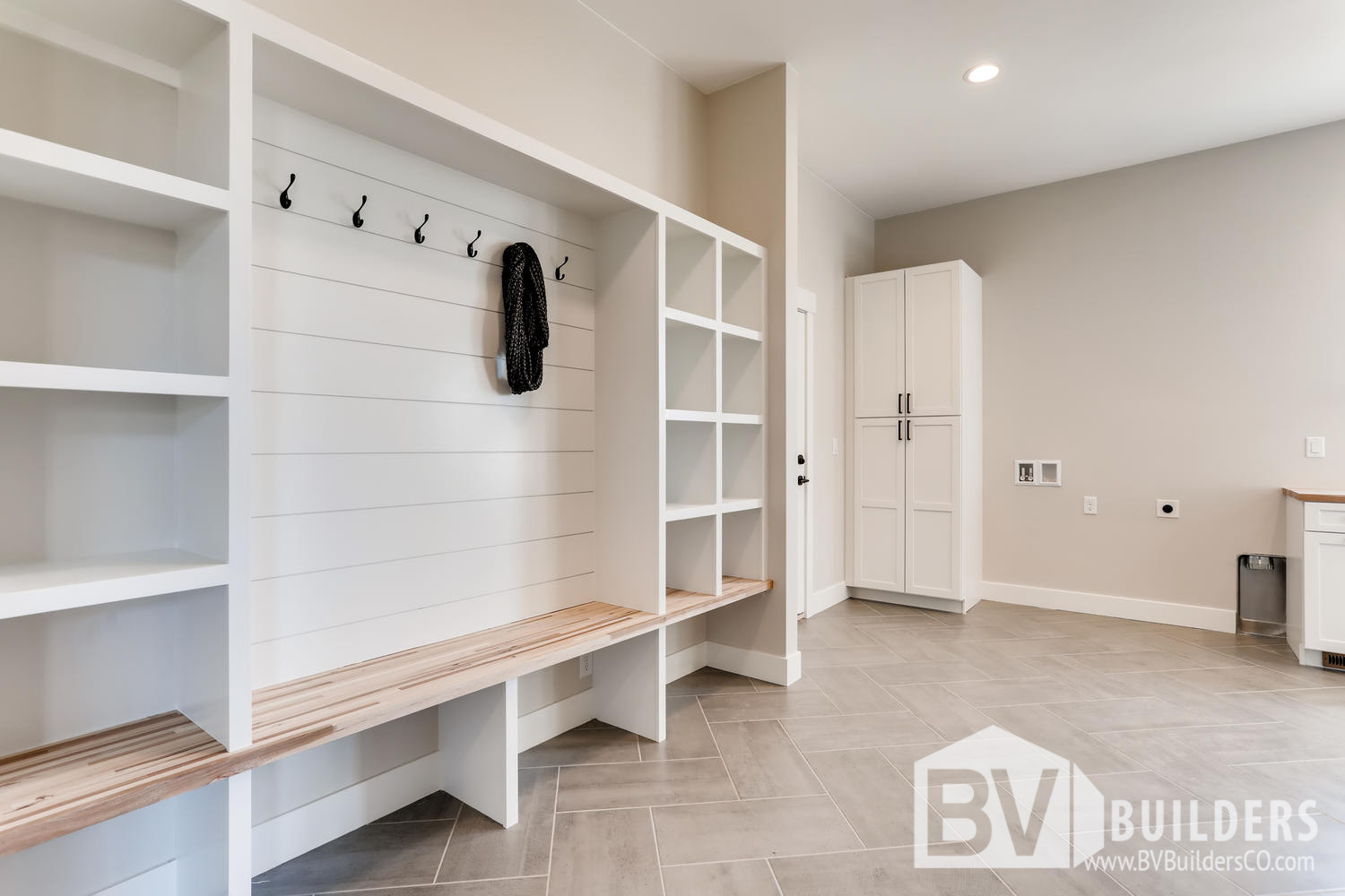 Mud room with built in bench, cubbies and shiplap coat hook wall