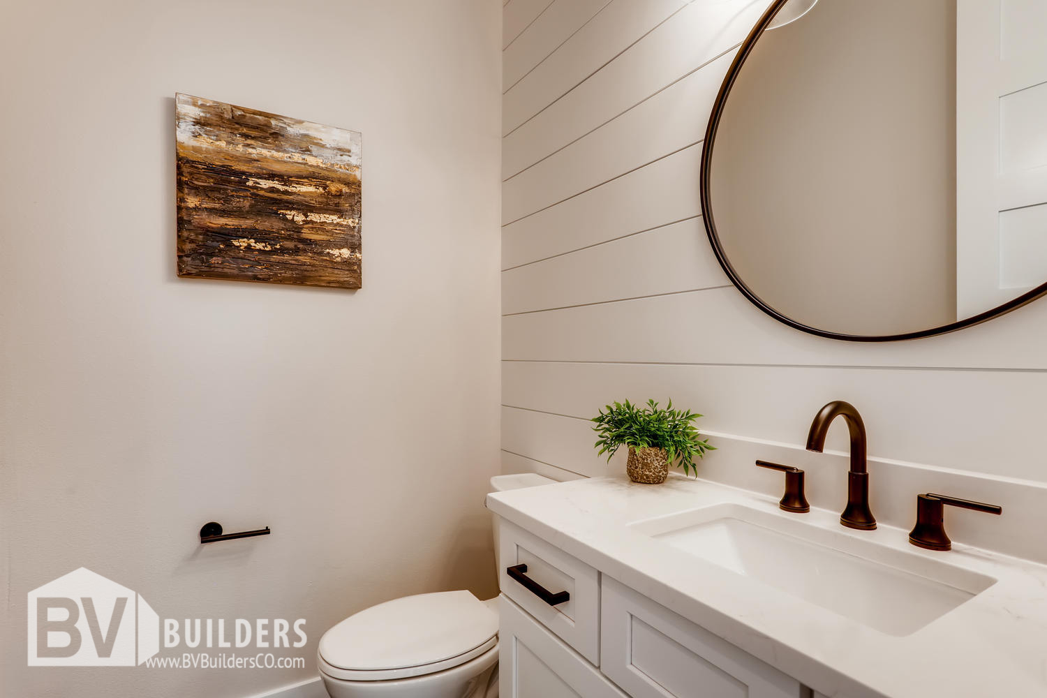 Powder room with shiplap wall and circular round mirror