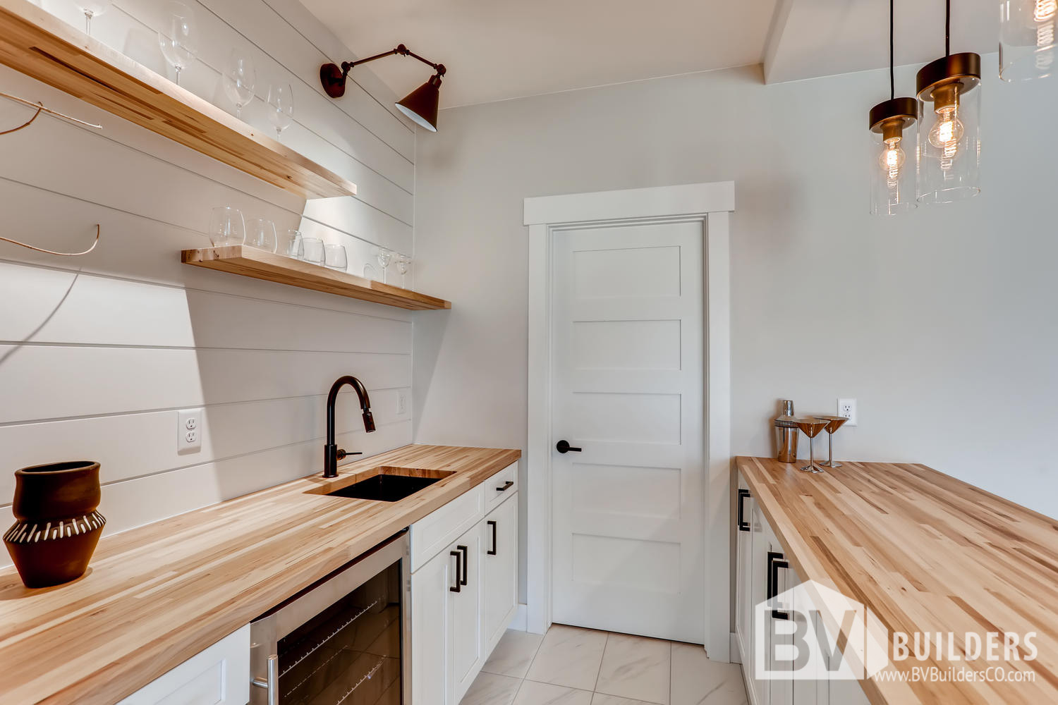 Butcher block wet bar with floating shelves, shiplap backsplash and bar sink